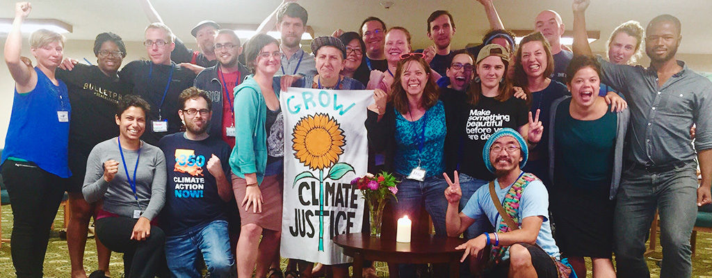 "A multiracial group of two dozen young adults cheers and holds a banner that says ""Grow Climate Justice"""
