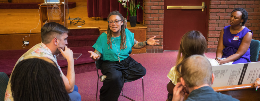 Sara Green, a young Black woman, animatedly speaks in a small group of people