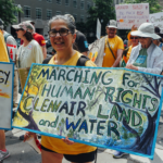 "A person marches with a sign that says ""Marching for Human Rights, Clean Air, Land, and Water"""