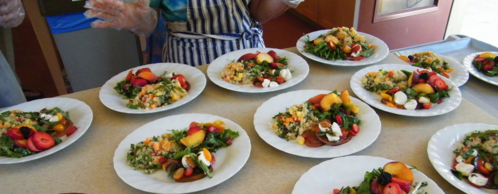 A person in an apron stands over plates of couscous, salad, and fruit
