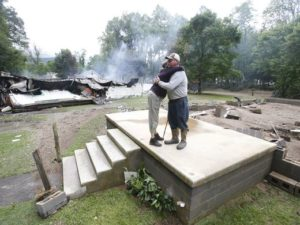 Jimmy Scott gets a hug from Anna May Watson, left, as they clean up from severe flooding in White Sulphur Springs, W. Va., June 24, 2016. Scott lost his home to the flood and a fire that consumed his and the homes of several relatives. Steve Helber, AP