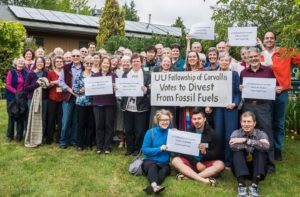 UUFC's first climate justice project: The Rev. Jill McAllister (center, behind large sign) and a few members of the Unitarian Universalist Fellowship of Corvallis celebrate their decision to divest from fossil fuels. [Photo courtesy of Mina Carson.]