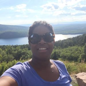 A photo of Elandria Williams smiling on a bluff wih a background of trees, water, mountainsides, and a bright blue sky