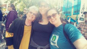 Pictured: UUMFE Treasurer Ellen McClaran, Office Administrator Sabrina Louise, and Program Director Aly Tharp smiling and hugging together for a photo at the #AllEyesonJuliana rally